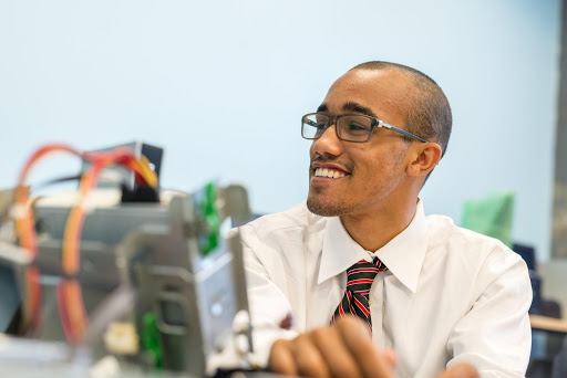 Smiling student holds up computer parts.