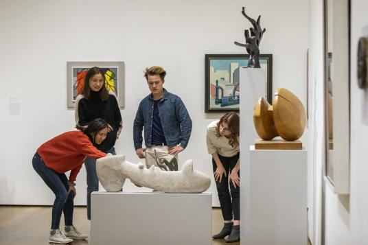 Students study art objects in an art gallery