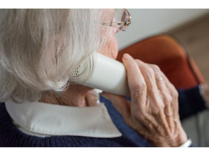Photo of a senior adult using a telephone.