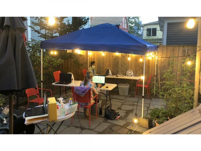 Evening in the backyard, two women on computers, socially distanced.