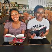 Two high school students read in a library.