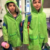Two children in matching bright green raincoats stand with backpacks in-hand.