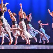 A group of dancers in black shirts and white skirts leap through the air on stage.