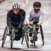 Two athletes compete in a race on cycles.