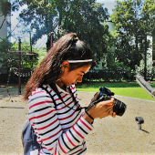 A young photographer observes the photo she just took outside at a park.