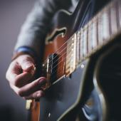 A close-up of someone playing a guitar.