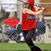 A softball player steps into her swing as she watches the ball approaching.