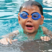 A child wearing goggles emerges from a pool.
