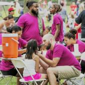 A group of volunteers in pink shirts work at a face-painting station for kids.