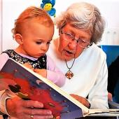 A grandparent and infant read a book together.