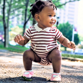 A baby standing in a park.