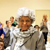 An older woman poses for a photo while receiving a standing ovation.