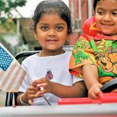 A preschool girl holds a flag and a preschool boy drives a toy truck.