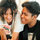 Two teenagers smile while looking at something on a cell phone.